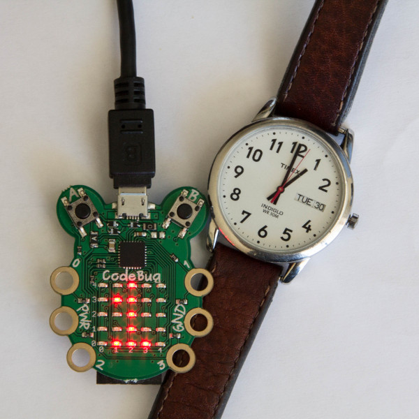 CodeBug in front of a clock
